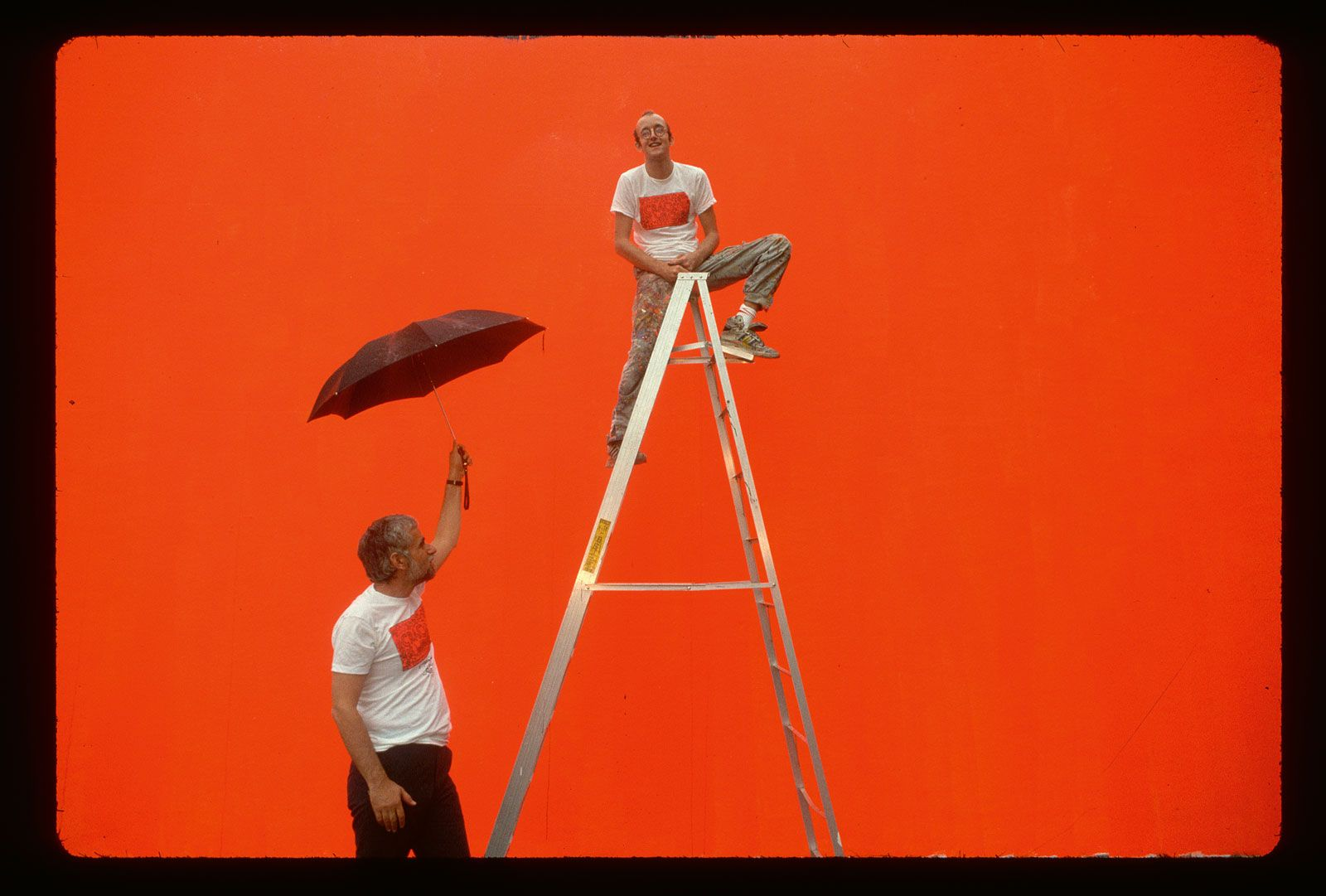 Keith Haring on a ladder, in front of the bright orange undercoat on which he would paint his mural Crack is Wack, with the New York Park Commissioner Henry Stern holding an umbrella